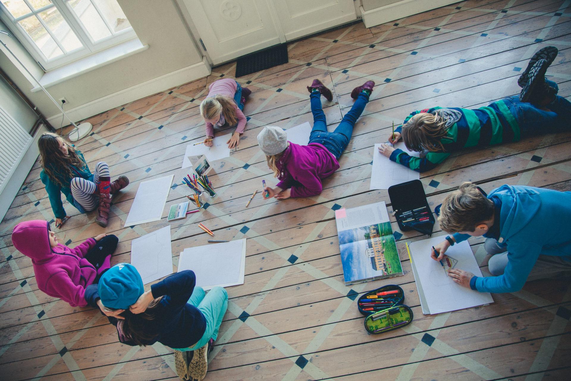 Kindern liegen im Entrée auf dem Boden und malen Florian Foest